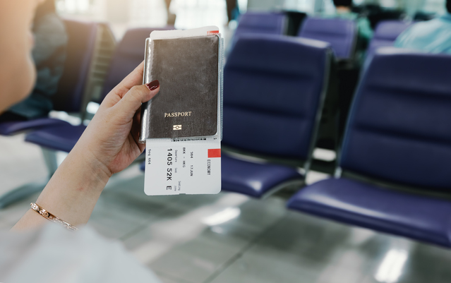 Woman hand holding passport and flight ticket in airport.